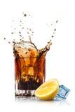 可乐飞溅在玻璃的用柠檬和冰 库存图片