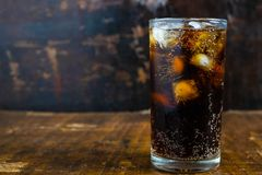 可乐饮料,在一块玻璃的黑汽水在桌上 图库摄影