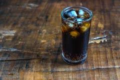 可乐饮料,在一块玻璃的黑汽水在桌上 免版税库存照片