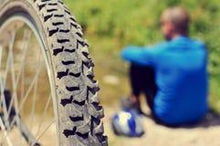 可及一些休息的骑自行车者与减速火箭的过滤器e的河沿 免版税图库摄影