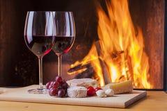 可口乳酪和酒在壁炉 图库摄影