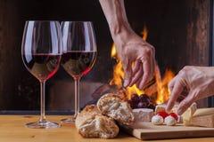可口乳酪和酒在壁炉 免版税库存照片