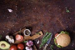 可口乳酪汉堡用牛肉小馅饼、乳酪、新鲜的莴苣、蘑菇和蕃茄在一个新鲜的小圆面包与芝麻籽 免版税库存照片