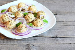 可口乳酪球用干草本和烤芝麻籽服务与洋葱圈和蓬蒿在板材 免版税库存照片