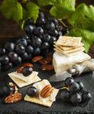 可口乳酪薄脆饼干开胃菜用葡萄和胡桃 免版税库存照片