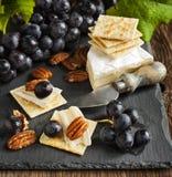 可口乳酪薄脆饼干开胃菜用葡萄和胡桃 免版税库存图片