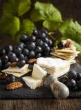 可口乳酪薄脆饼干开胃菜用葡萄和胡桃 免版税图库摄影