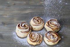 可口五个的片断和甜点被烘烤的玫瑰塑造了与苹果馅的酥皮点心在木背景搽粉用白砂糖 库存照片