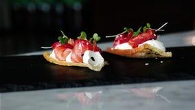 可口使bouche开胃菜、被治疗的三文鱼用甜菜根,棋和橙色开花发笑 免版税库存照片