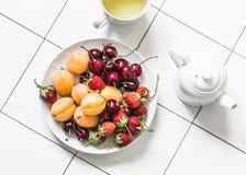 可口健康点心-新鲜的成熟果子和莓果草莓、杏子、樱桃和绿茶在轻的背景, 免版税库存照片
