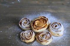 可口六个的片断和甜点被烘烤的玫瑰塑造了与苹果馅的酥皮点心在木背景搽粉用白砂糖 免版税图库摄影