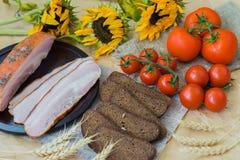 可口切片烟肉,黑麦黑面包,在麻袋布,老向日葵顶视图的成熟红色蕃茄 食物新鲜有机 图库摄影