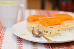 可口切片的特写镜头图象杏子蛋糕在有一个杯子的一块白色板材放置在桌上的可可粉 免版税库存照片