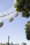 可口可乐伦敦眼在与树和伦敦天空锂的一个晴天 图库摄影