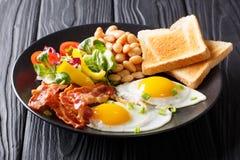 可口和丰盛的一餐:两个煎蛋用烟肉,豆, toa 图库摄影