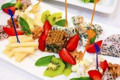 可口和美丽的点心在蜂蜜和乳酪果子做的餐馆  草莓猕猴桃乳酪 图库摄影