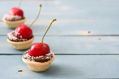 可口巧克力果子馅饼用一个樱桃和椰子在一张蓝色木桌上 免版税库存图片