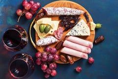 可口开胃菜用在蓝色背景的红葡萄酒 果子,乳酪,火腿,香肠 顶视图,平的位置 免版税库存照片