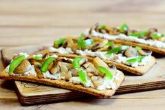 可口开胃菜用油煎的蘑菇和新鲜的绿色甜椒在一个木板 简单和热诚的素食快餐 图库摄影
