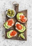 可口开胃菜用酒-乳脂干酪、熏制鲑鱼和鲕梨三明治和橄榄在一个木板 库存图片