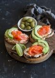 可口开胃菜用酒-乳脂干酪、熏制鲑鱼和鲕梨三明治和橄榄 图库摄影