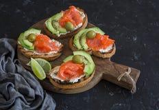 可口开胃菜用酒-乳脂干酪、熏制鲑鱼和鲕梨三明治和橄榄 免版税库存照片