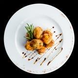 可口开胃被烘烤的蘑菇用在一块白色板材的调味汁 免版税库存图片