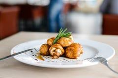 可口开胃被烘烤的蘑菇用在一块白色板材的调味汁 免版税库存照片