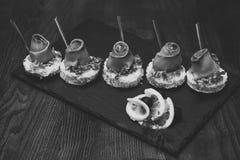 可口快餐在黑盘的餐馆服务 冷的开胃菜,与红色鱼,木背景的点心 点心 库存照片