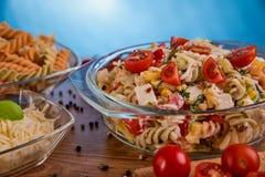 可口意大利面制色拉或地中海沙拉 蕃茄用无盐干酪蓬蒿玉米香料和橄榄油在一张木桌上 免版税库存图片