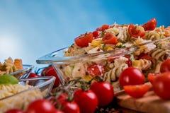 可口意大利面制色拉或地中海沙拉 蕃茄用无盐干酪蓬蒿玉米香料和橄榄油在一张木桌上 图库摄影