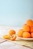 可口成熟橙色杏子垂直的照片在一块明亮的板材的在与绿色餐巾的木桌上在浅兰的墙壁背景 免版税库存照片