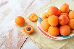 可口成熟橙色杏子顶视图在一块明亮的板材的在与绿色餐巾的木背景 新鲜的水多的果子 免版税图库摄影