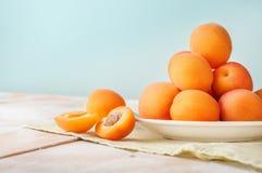 可口成熟橙色杏子水平的看法在一块明亮的板材的在与绿色餐巾的木桌上在浅兰的墙壁上 免版税库存照片