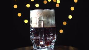 可口手制作了烈性黑啤酒,搬运工或黑啤酒涌入一个玻璃杯子 股票录像