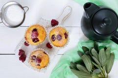 可口新近地被烘烤的松饼用莓,装饰用搽粉的糖,茶壶 图库摄影
