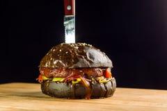 可口新鲜的家庭做的牛肉汉堡特写镜头用莴苣、乳酪、葱和蕃茄 黑小圆面包 免版税库存照片
