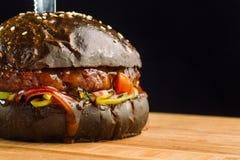 可口新鲜的家庭做的牛肉汉堡特写镜头用莴苣、乳酪、葱和蕃茄 黑小圆面包 图库摄影
