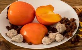 可口新鲜的柿子果子、葡萄干和干无花果在板材和木桌 库存照片