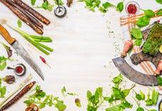可口新鲜蔬菜、香料和调味料鲜美烹调的与厨刀在白色木背景,顶视图,框架 免版税库存照片
