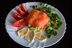 可口新鲜食品板材用海鲜、乳酪和salat 三文鱼冠上了用鱼鱼子酱,在白色板材的膳食在黑背景 免版税库存照片
