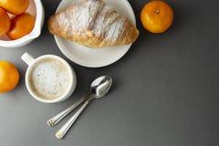 可口早餐咖啡用新月形面包和柑橘水果-桔子 早晨咖啡因 法国,新鲜的酥皮点心和咖啡或 库存照片