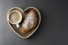 可口早餐咖啡用新月形面包 心形的配件箱 早晨咖啡因 法国,新鲜的酥皮点心和咖啡或拿铁 免版税库存照片