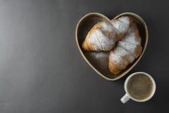 可口早餐咖啡用新月形面包 心形的配件箱 早晨咖啡因 法国,新鲜的酥皮点心和咖啡或拿铁 免版税图库摄影