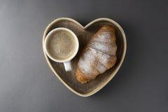 可口早餐咖啡用新月形面包 心形的配件箱 早晨咖啡因 法国,新鲜的酥皮点心和咖啡或拿铁 免版税库存图片