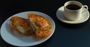 可口早餐无奶咖啡、鲕梨三明治、鸡蛋和乳酪在黑暗的背景 免版税库存图片