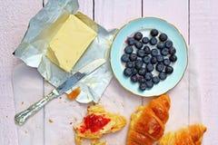 可口早餐用新鲜的新月形面包和成熟莓果在老木背景,选择聚焦 免版税图库摄影
