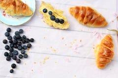 可口早餐用新鲜的新月形面包和成熟莓果在老木背景,选择聚焦 免版税库存图片