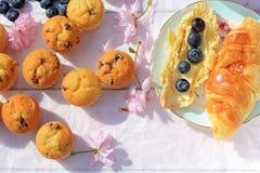 可口早餐用新鲜的新月形面包和成熟莓果在老木背景,选择聚焦 免版税库存照片