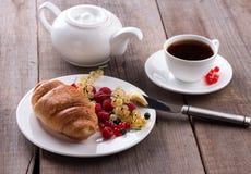 可口早餐用新鲜的新月形面包和成熟莓果 免版税图库摄影